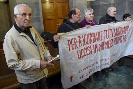 Vito Bitetti (S), un lavoratore ammalatosi a causa dell'amianto e costituitosi parte civile, con alcuni aderenti del comintato per la difesa della salute nei luoghi di lavoro al termine della lettura della sentenza, 21 marzo 2016. ANSA/DANIEL DAL ZENNNARO